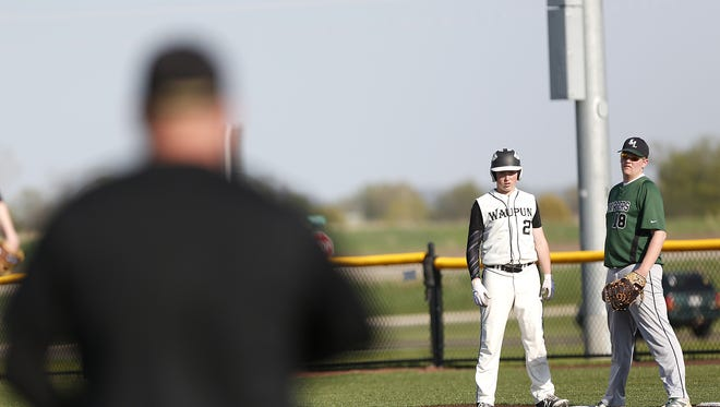 A Waupun base runner looks down to the third base coach for signs during a game against Kettle Moraine Lutheran.