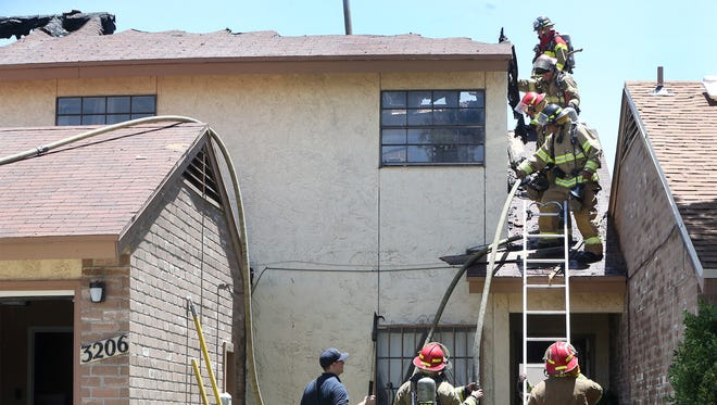 El Paso firefighters descend from the roof of a duplex along the 3200 block of Isla Bahia Way after extinguishing a fire there around noon Wednesday in East El Paso. Half of the duplex caught fire, causing an unknown amount of damage. The occupants of one side were not home when the fire happened, while the occupants of the second unit were able to evacuate safely, said Fire Department public information officer Enrique Aguilar. Thirteen fire units and 36 personnel responded to the blaze, Aguilar said.