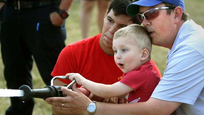 Oliver Voisin, 3, tries his hand at a fire house with his dad, Joel, and Greenfield Fire Department intern Mark Lyman during Greenfield's National Night Out at Konkel Park in 2015.