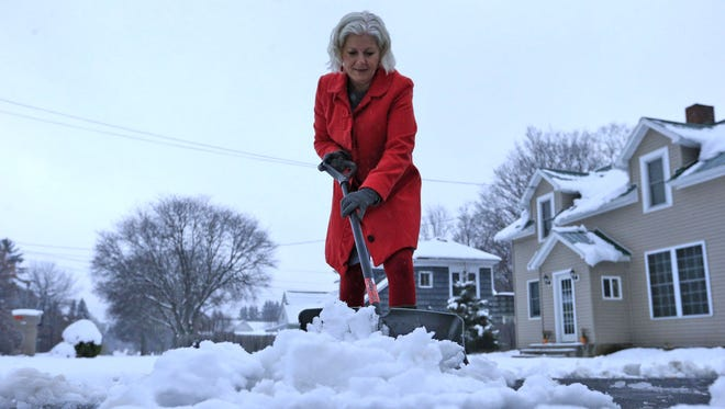 Lynette Johnson clears snow in front of her Mill Street home on Nov. 17 in Springville, N.Y.