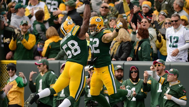 Green Bay Packers linebacker Clay Matthews (52)  celebrates with teammate Sam Barrington (58) after Matthews making a pick six past Carolina Panthers receiver Jerricho Cotchery (82) during Sunday's game at Lambeau Field. The play was reversed due to a pass interference call on Packers' Tramon Williams. Evan Siegle/Press-Gazette Media