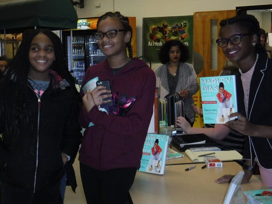 Author Marley Dias poses with students at her exhibit