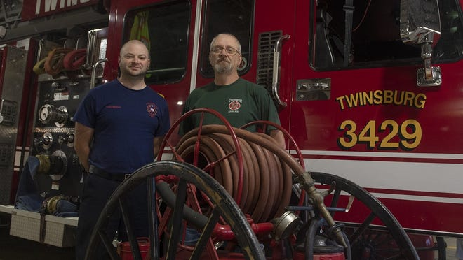 Four generations of the Davet family have been firefighters with the Twinsburg Fire Department. Bob K. Davet, left, stands with his father, Robert I. Davet, with the department's original 1919 fire hose.