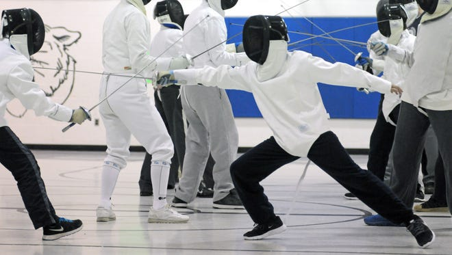 Ruben Garcia, 12, of Fort Gratiot lunges forward to make a touch Monday, Mar 2, during fencing club practice at Trinity Lutheran church in Port Huron.