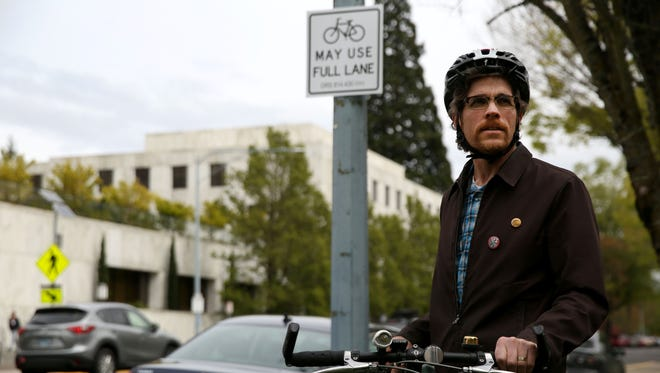 Cyclist David Fox stands next to a sign he made and placed on a light post along State Street in Salem, on Monday, April 6, 2015.