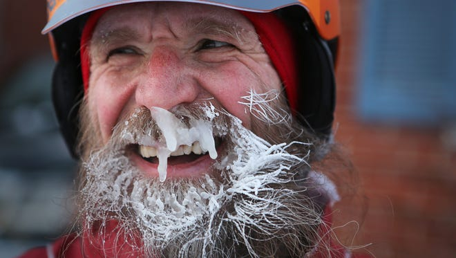 """In a Feb.19, 2014 photo, Fraser Cunningham, 56, a General Electric engineer, arrives home in Madeira, Ohio, with ice that has formed on his beard, which is a product of freezing water vapors produced from breathing. Cunningham calls it his """"chinsulation."""" Cunningham hasn't missed a day biking to and from work for a year and a half."""