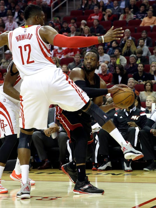 Miami Heat's Dwyane Wade, right, tries to pass the ball as Houston Rockets' Dwight Howard (12) defends during the first quarter of an NBA basketball game, Saturday, Jan. 3, 2015, in Houston. (AP Photo/David J. Phillip)