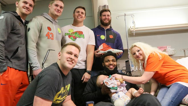 Clemson football players, from left, Austin Spence, Chad Smith, Daniel Funderburk, Isaac Moorhouse, Sean Pollard, stand near teammate Christian Wilkins holding one-year old Hudson Belviso of Spartanburg, near his mother Kaci Belviso, on Thursday at the Shriners Hospitals for Children in Greenville.