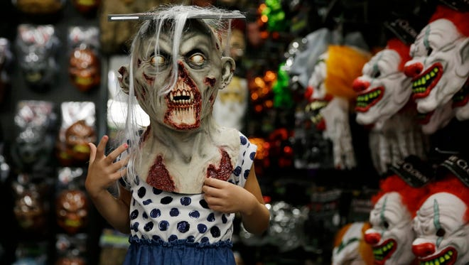A shopper tries on an zombie mask.