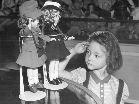 1942: Marilyn Slaymaker, 5, salutes a pair of dolls in the Younkers Toyland and then tried to decide which one she would rather have for Christmas.