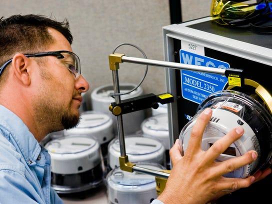 A technician tests a smart meter at the Arizona Public