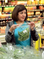 H-E-B Slim Down Showdown contestant Jane Alvarez asks the dietitian about some string beans during a pantry makeover at the H-E-B Plus! on Saratoga Boulevard in late January.