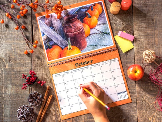 Open wall calendar with rustic October image, female hand ready to write in square with pencil