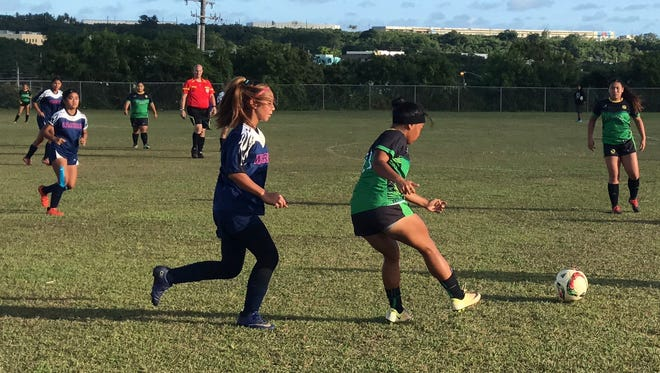 The St. Paul Warriors played the John F. Kennedy Islanders  in a IIAAG Girls Soccer playoff game on May 10. Trailing the Islanders player is Warriors Tiffany Lopez.