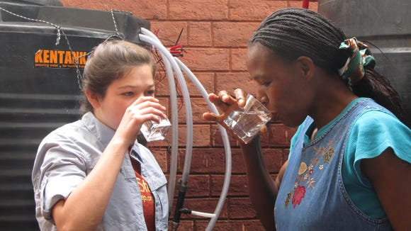 Emma Rider drinking the first glass of clean water with a Kenyan orphanage owner after installing a chlorinator.