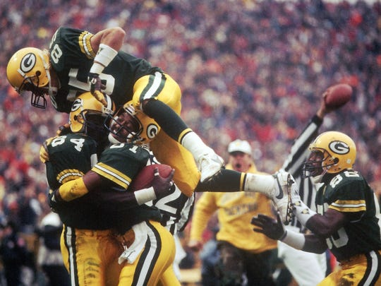 Green Bay Packers receiver Sterling Sharpe (84) is mobbed by fellow wide receivers Perry Kemp (81), Jeff Query (85) and Aubrey Matthews (88) after scoring the game-winning touchdown against the Chicago Bears at Lambeau Field on Nov. 5, 1989. The Packers won 14-13.