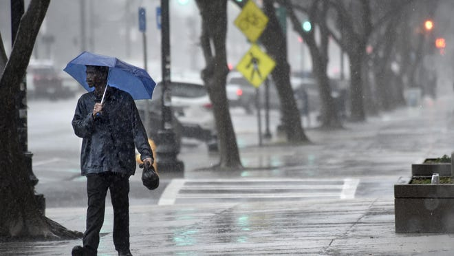 A man tries to stay dry under his umbrella as he walks down Broad Street during a heavy rain shower in Augusta, Ga., Thursday afternoon February 6, 2020.