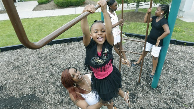 Tyesha Boone holds her daughter Tahani Smith, 4, as in the background her two other daughters, Trinity Turner, 12, and Ty-Shiera Tillard, 9, chat at the playground of Crerand Commons in Gates. Boone raised her three daughters there.