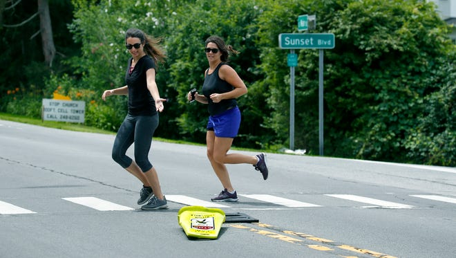 Brooke Gazdag of Munich, Germany, jogging with her sister Lyndsey Ploof of Vero Beach, FL, points at a crosswalk sign knocked earlier by a truck on the corner of South Main Street and Sunset Boulevard in Pittsford, where an elderly man was killed recently. The sisters were visiting their parents who live in Pittsford.