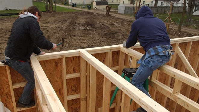 Volunteers work on construction of a local Habitat house in this file photo.