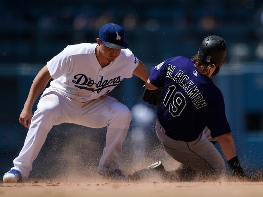 Los Angeles Dodgers shortstop Corey Seager, left, tags out Colorado Rockies' Charlie Blackmon, right, as he attempts to steal second base during the sixth inning of a baseball game in Los Angeles, Sunday, July 3, 2016. (AP Photo/Kelvin Kuo)