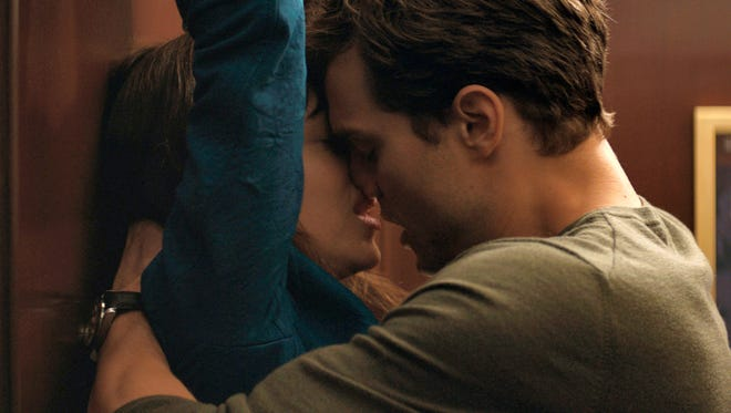 "Dakota Johnson, left, and Jamie Dornan appear in a scene from ""Fifty Shades of Grey."""