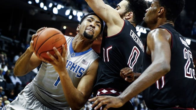 University of Memphis forward Dedric Lawson (left) drives to the basket against Temple University defenders Obi Enechionyia (middle) and Damion Moore (right) during first half action at FedExForum.