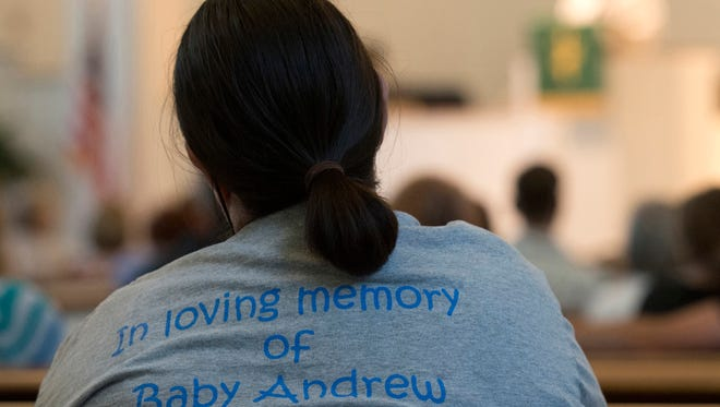 A family member listens to speaker Jerri Hana, board president of Capital Area Healthy Start Coalition, during a service to remember and honor National Pregnancy and Infant Loss Awareness Day. The service at, St. Paul's Methodist Church, was followed by a candle-lit walk around Lake Ella.