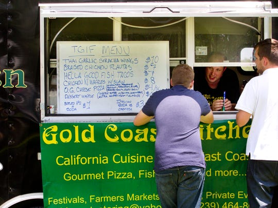 Steve Shinn, the owner of the Gold Coast Kitchen, a mobile food trailer, takes an order from some of his customers on Friday.