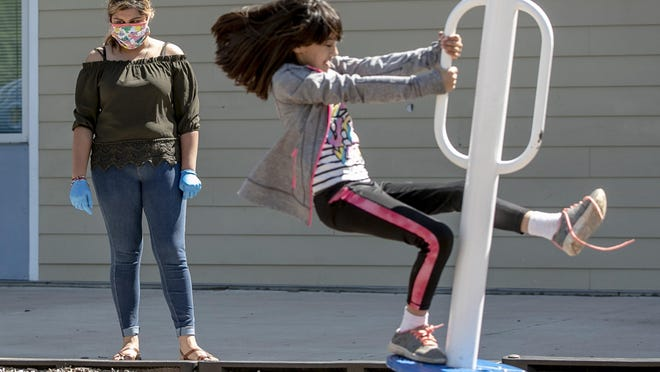 Lorena Dominguez, a campus operations specialist at the IDEA Rundberg charter school, watches second grader Leeyah Patten play on April 1. The State Board of Education on Friday approved two charter operators' plans to open campuses within the Austin and Hays district boundaries.