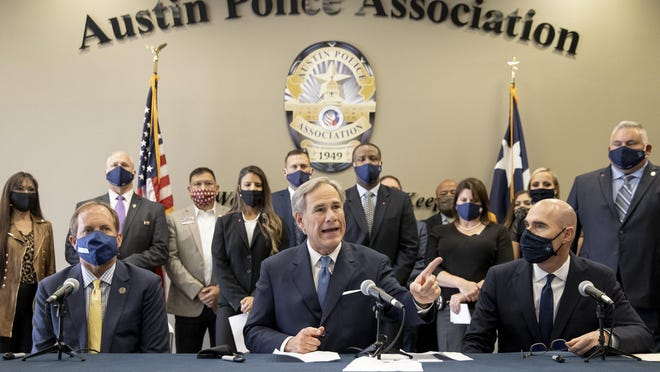 """Gov. Greg Abbott speaks at a news conference with Texas Attorney Geberal Ken Paxton, left, and House Speaker Dennis Bonnen before signing a """"Texas Backs the Blue Pledge"""" at the Austin Police Association on Sept. 10."""