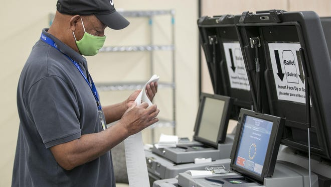 Travis County elections field support technician Keith Rogers tests a ballot scanner at the Travis County Clerk office on Oct. 12.