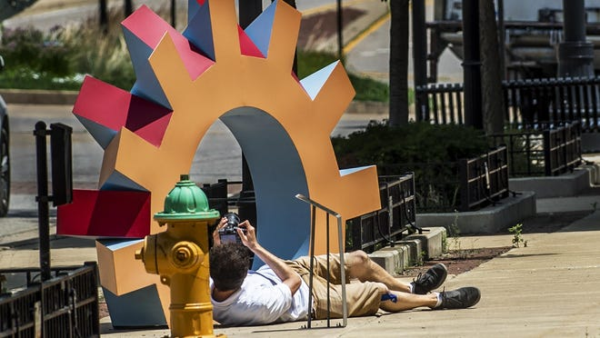 With final installation of the newest pieces complete, Videogenique owner Raphael Rodolfi goes low for an angle from which to work while producing a video Thursday, July 2, 2020 for ArtsPartners that will provide viewers with a virtual tour of Sculpture Walk along Washington Street in downtown Peoria.
