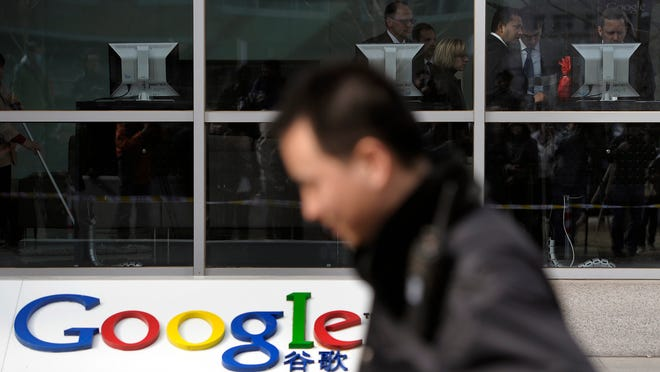 A security guard walks past while foreign visitors are seen inside the Google China headquarters in Beijing in March 2010. Connections to Google Inc.'s popular e-mail service have been blocked in China amid efforts by the government to limit access to the company's services.