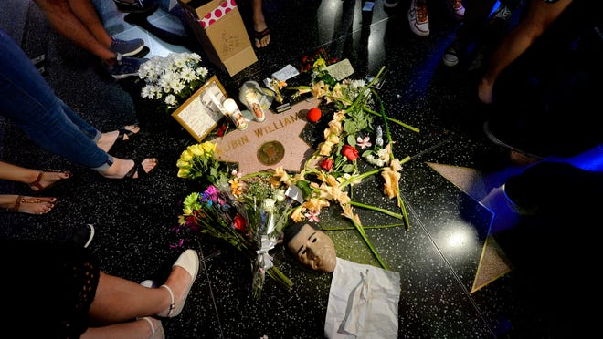 Flowers are placed in memory of actor/comedian Robin Williams on his Walk of Fame star on Monday in Hollywood. Williams, a brilliant shape-shifter who could channel his frenetic energy into delightful comic characters, died Monday in an apparent suicide. He was 63.