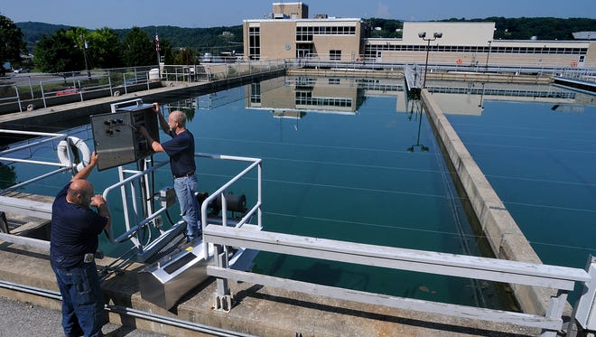 In this 2014 file photo, Joseph Marcinelli, foreground, head maintenance mechanic, and Brian Morris, maintenance supervisor, troubleshoot sludge vacuum controls in this view looking west toward the Poughkeepsies' Water Treatment Facility, adjacent to the Marist College campus along the Town of Poughkeepsie waterfront. Ongoing upgrades at the plant are reducing the precursors to disinfection byproducts, which has led to better water quality in the Greenbush district.