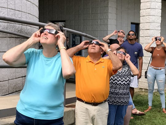 Residents look through special protective sunglasses