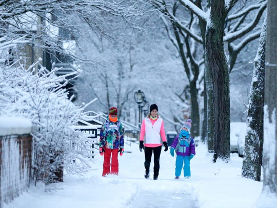 Vesla Hoeschen (center) of Milwaukee walks in the snow with her children, Audrey (left), 12, and Ella, 6, along Lake Drive in Milwaukee. They were on their way to school. Many kids are hoping with the snow forecast school will be closed on Friday.