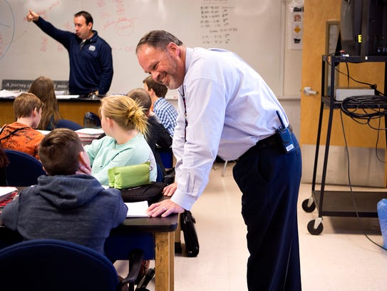 Principal Leland Blankenship talks with a student in