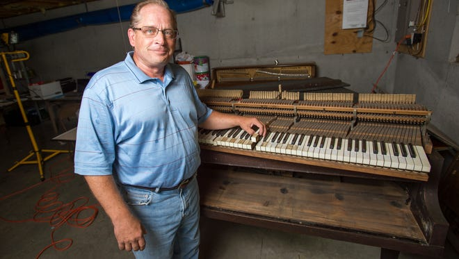 Rick Pedro with a 1917 Harrington grand piano that he is restoring in the basement of his Apalachin home.
