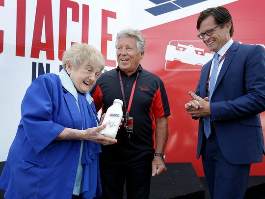 Eva Kor is presented with a bottle of milk from Mario Andretti and IMS president Doug Boles on May 22, 2017, at the Indianapolis Motor Speedway.
