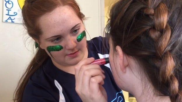 Loyola's Sarah Szwak put eye-black on a teammate.
