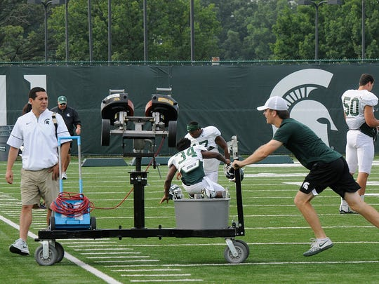 An MSU student equipment manager moves a cart during
