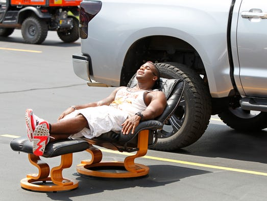 Buffalo Bills safety Aaron Williams takes a few moments to soak up some sun in the parking lot before moving into his dorm room as players arrive for the start of training camp.