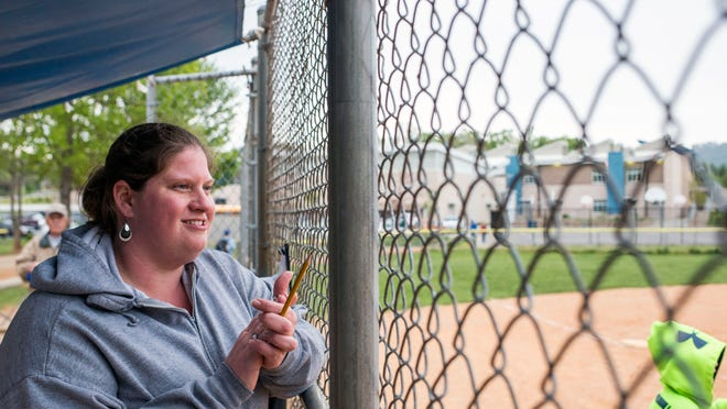 Francine Weinhagen watches her daughter's softball game. The mom of two started out as a single parent with limited education. She has now gone back to school and works as a nurse while raising her kids with a partner.