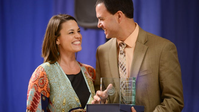Christopher Nye, a teacher at Northeast Middle School, stands with Principal Teresa Tritt as he is recognized as the JMCSS-WTH Foundation Teacher of the Year during an annual luncheon Thursday at the Carl Perkins Civic Center.