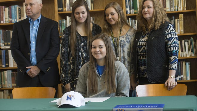 Catholic High School student, Abby Herrmann, seated, signs a golf scholarship with the University of Memphis during a ceremony at the school Monday morning, while her family looks on.