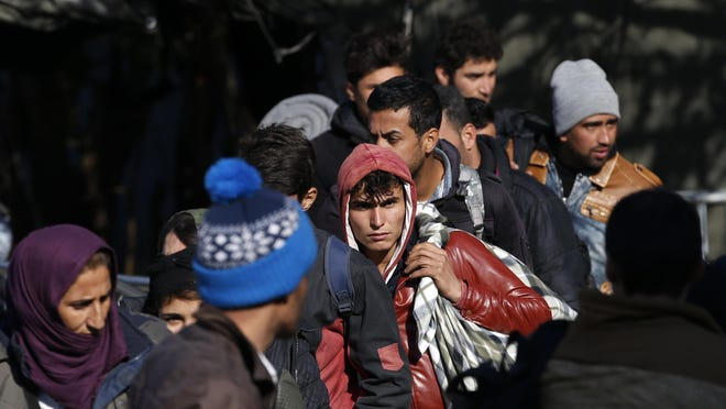 Migrants wait to register with the police at the refugee center in the southern Serbian town of Presevo, Monday, Nov. 16, 2015. Refugees fleeing war by the tens of thousands fear the Paris attacks could prompt Europe to close its doors, especially after police said a Syrian passport found next to one attacker's body suggested its owner passed through Greece into the European Union and on through Macedonia and Serbia last month. (AP Photo/Darko Vojinovic)