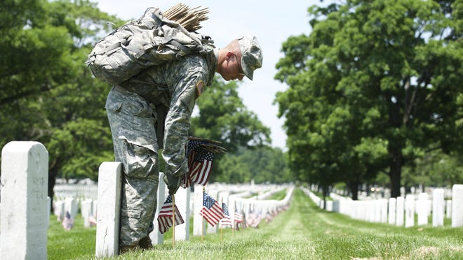 A soldier places a flag at a grave in Arlington National Cemetery for Memorial Day as part of the annual Flags In Ceremony.
