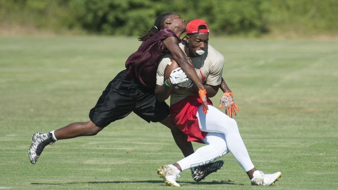 Escambia High School's Jacob Copeland, right, fights off a Pensacola High School defender during a 7-on-7 game at Ashton Brosnaham Park in 2016.
